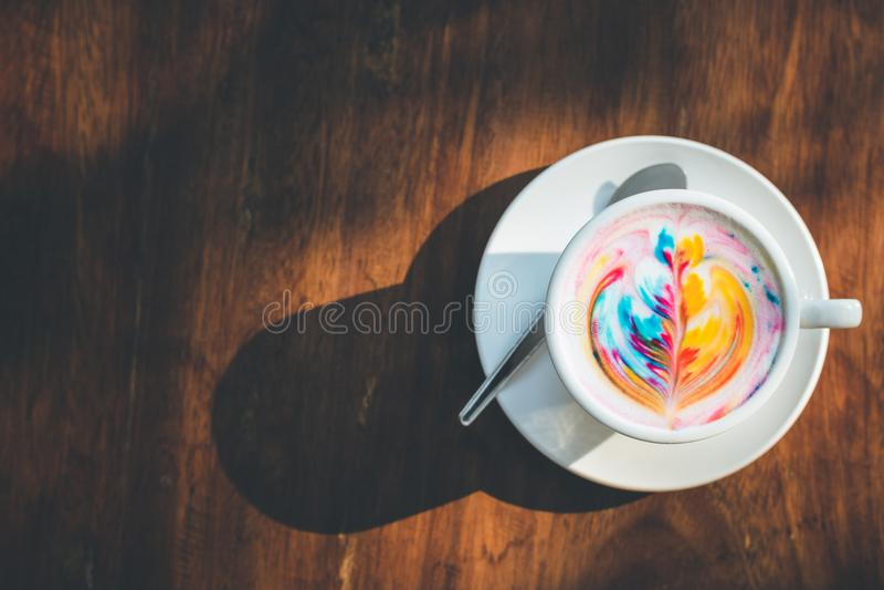 Bunter Regenbogen Lattekaffee in der weißen Schale auf Holztisch mit stockfotos