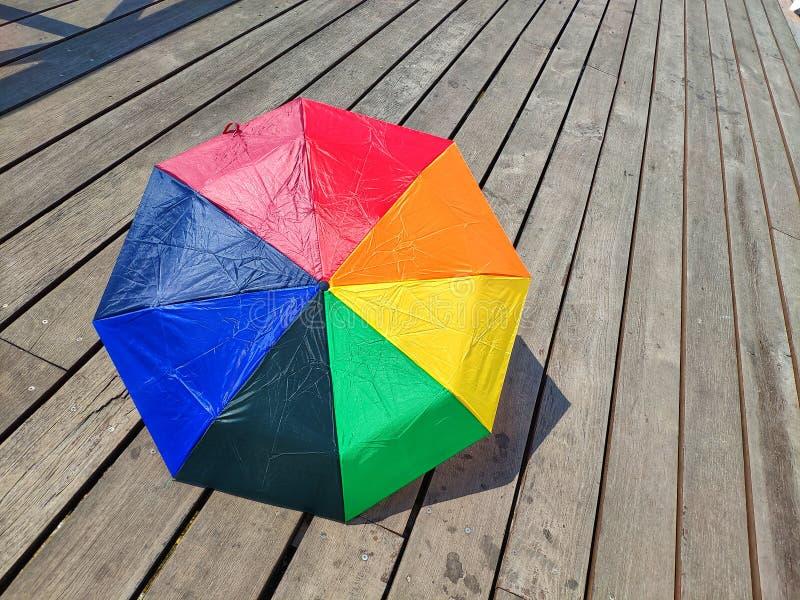 Bunter Regenschirm auf Bretterboden, am Sommertag Seashells gestalten auf Sandhintergrund lizenzfreie stockfotografie