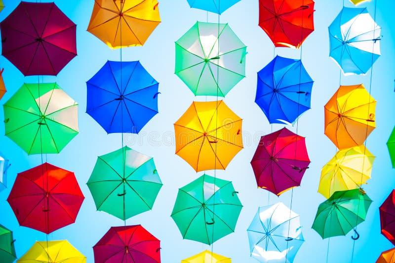 Bunter Regenschirm unter blauem Himmel, bunte Regenschirmkunstinstallation in einem Stadtzentrum, viele bunten Regenschirme in de stockbilder