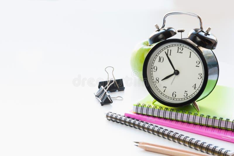 Bunter Schulbedarf, Buch und Wecker auf Weiß Abschluss oben Zurück zu Schule stockbilder