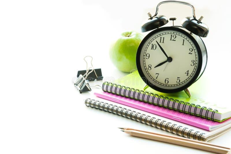 Bunter Schulbedarf, Buch und Wecker auf Weiß Abschluss oben Zurück zu Schule lizenzfreie stockbilder