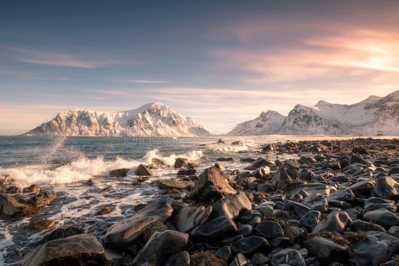 Bunter Sonnenaufgang des Schneegebirgszugs mit der Welle, die auf Küstenlinie an Skagsanden-Strand schlägt lizenzfreie stockbilder