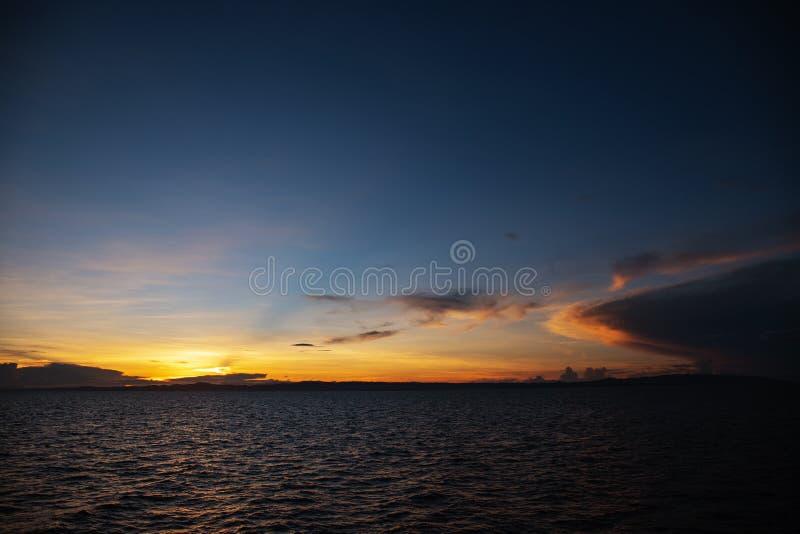 Bunter Sonnenaufgang mit blauem Himmel, orange Wolken und geplätschertem Meer Orange blaues skyscape am frühen Morgen stockfotos