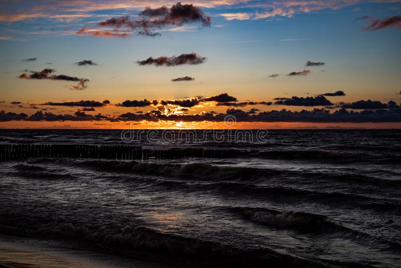 Bunter Sonnenuntergang über der polnischen Ostsee mit Wolken und Wellenbrecher des bewölkten Himmels lizenzfreie stockfotos