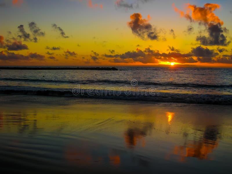 Bunter Sonnenuntergang, der über das Meer nachdenkt stockfotos