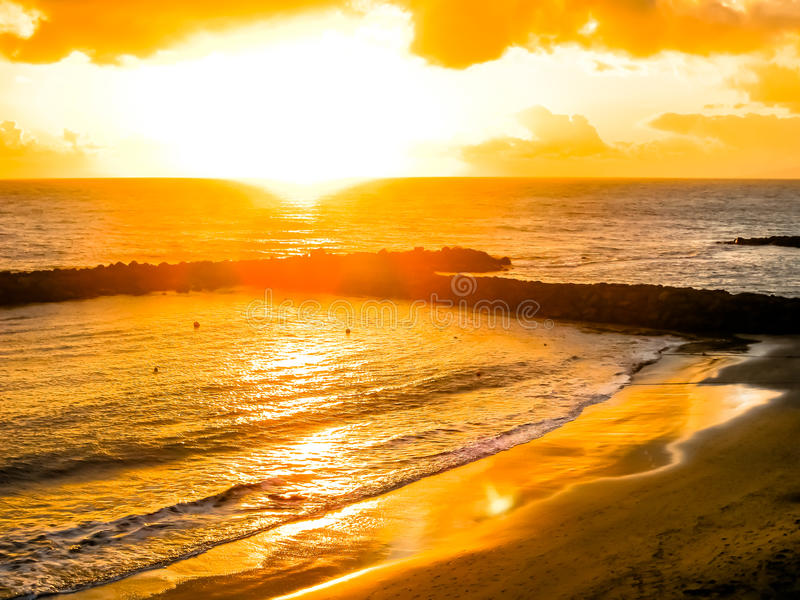 Bunter Sonnenuntergang durch den Ozean und den Strand stockbild