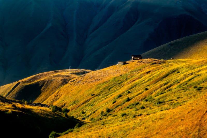 Bunter Sonnenuntergang mit Bergwiesen und Hütte in Kaukasus, Kazbegi, Land von Georgia lizenzfreies stockbild