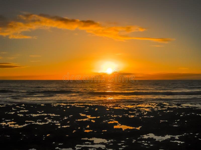Bunter Sonnenuntergang mit Wolken durch den Ozean lizenzfreie stockbilder