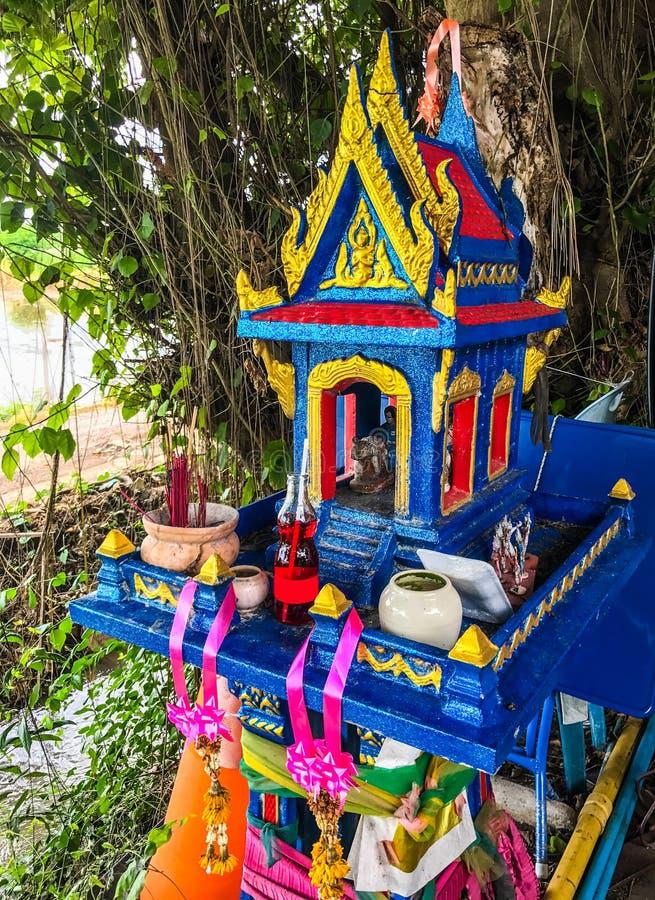 Bunter traditioneller thailändischer Geisthausschrein im Freien mit Blumengirlanden unter dem Baumschatten stockfoto