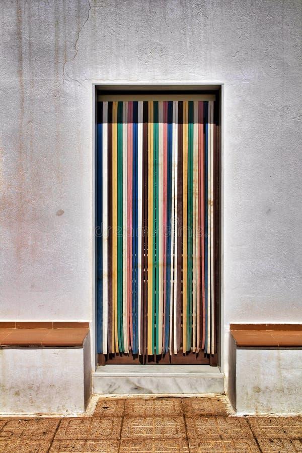 Bunter und gestreifter Vorhang auf Tür des Dorfhauses lizenzfreies stockfoto