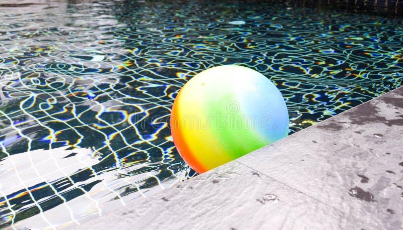 Bunter Wasserball, der in einen blauen Swimmingpool schwimmt stockfotos