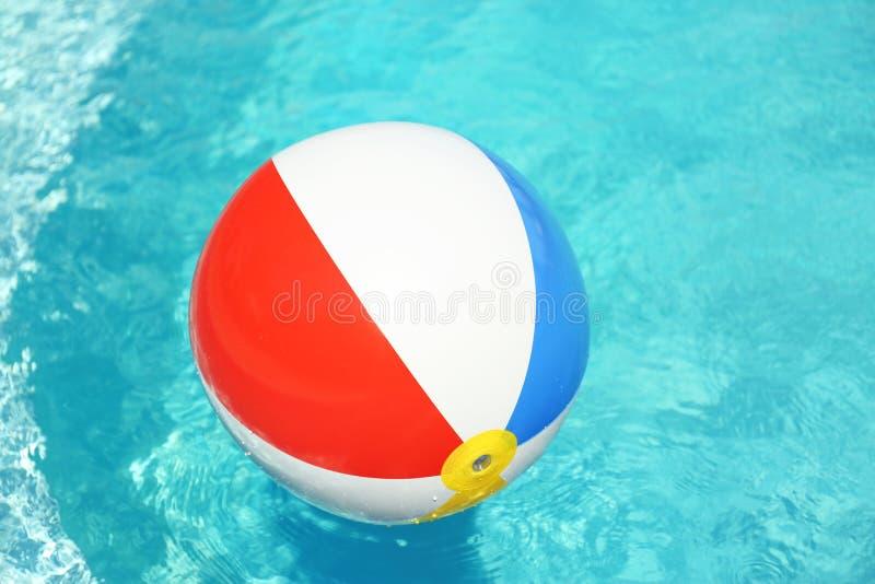 Bunter Wasserball, der in Swimmingpool am sonnigen Tag schwimmt stockbild