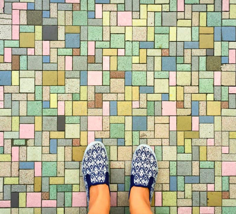 Bunter Ziegelsteinhintergrund und weibliche Füße Frau ` s Beine in den weißen und blauen Textilschuhen stockfoto