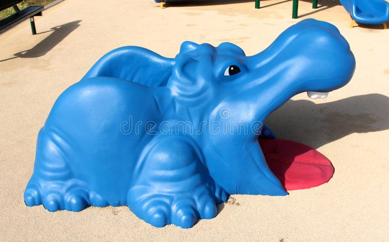 Buntes blaues und rotes Nilpferd-Spielzeug auf dem Spielplatz der Kinder lizenzfreie stockfotos