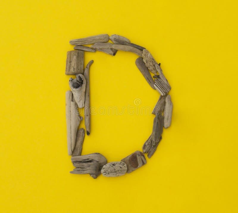 Buntes Buchstabe ` d ` gemacht von den hölzernen Stöcken auf gelbem Hintergrund stockfotos