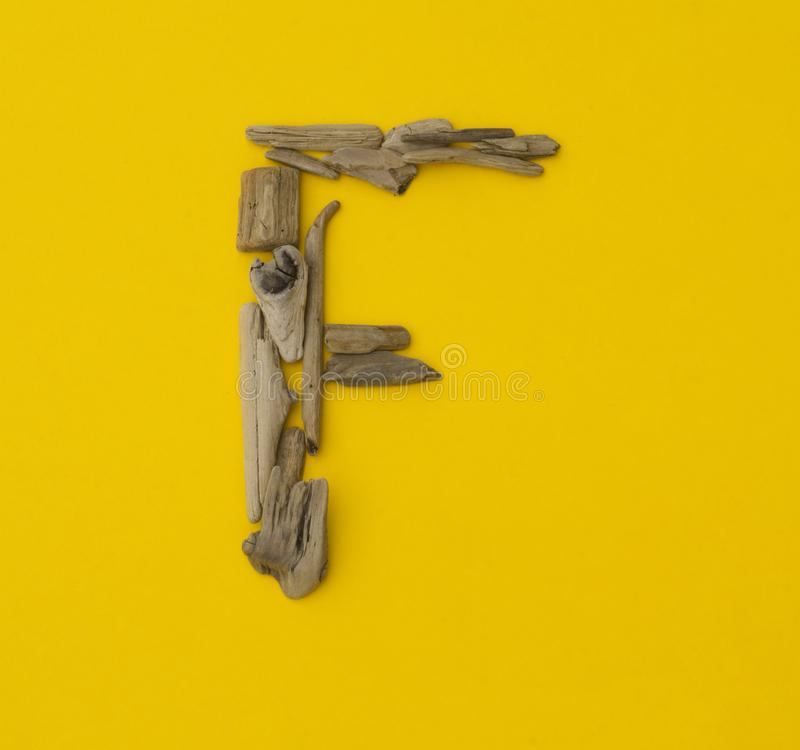 Buntes Buchstabe ` f ` gemacht von den hölzernen Stöcken auf gelbem Hintergrund stockfotos