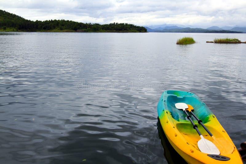 Buntes canoeing oder Kajakboot mit dem Paddel zwei, das auf See schwimmt stockfoto