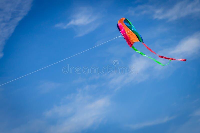 Buntes Drachenfliegen gegen einen blauen Himmel stockbilder