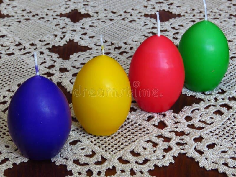 Buntes Ei formte Kerzen auf handgemachter Tischdecke in der Häkelarbeit Ostern-Inneneinrichtung lizenzfreies stockbild
