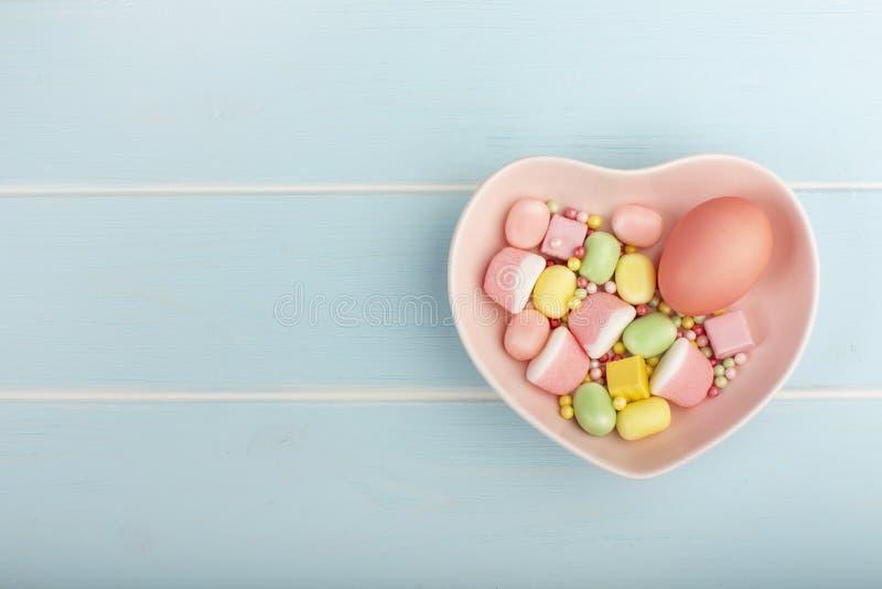 Buntes Ei Ostern auf einem Teller in Form von Herzen mit Bonbons lizenzfreies stockfoto