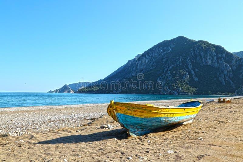 Buntes Fischerboot an einem Mittelmeerstrand mit Bergen im Hintergrund stockbilder