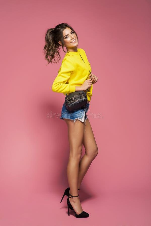 Buntes Foto des weiblichen Modells aufwerfend mit einer Tasche stockfotografie