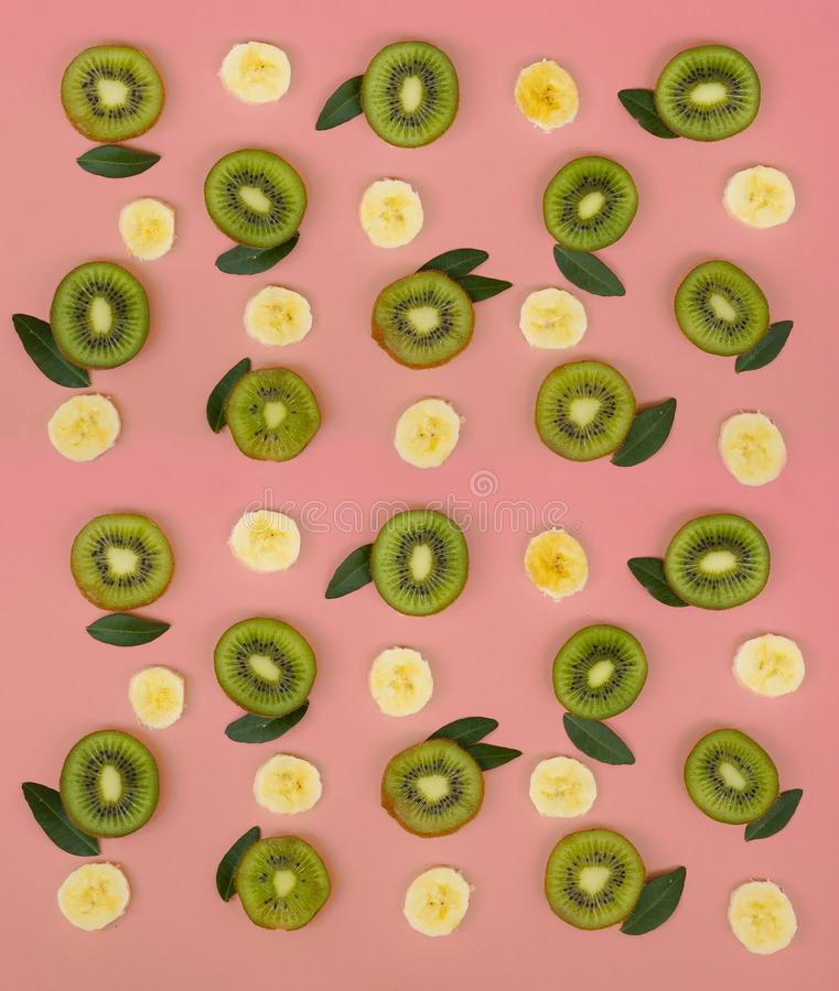 Buntes Fruchtmuster von neuen Kiwi- und Bananenscheiben auf rosa Hintergrund stockbilder