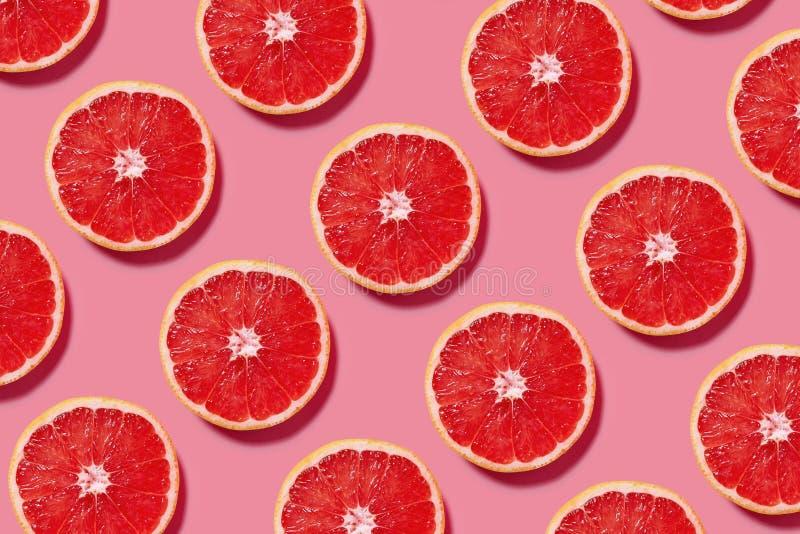 Buntes Fruchtmuster von neuen Pampelmusenscheiben auf rosa Hintergrund lizenzfreie stockfotos
