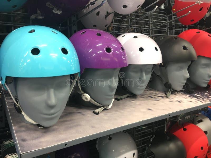 Buntes Gesch?ft Sturzhelm des Motorrades auf den Regalen Mehrfarbige schützende Fahrradsturzhelme im Geschäft Ein Mannequin, das  stockfotografie