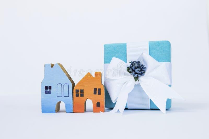 Buntes hölzernes Miniaturhaus und Geschenkbox auf weißem Hintergrund stockbilder