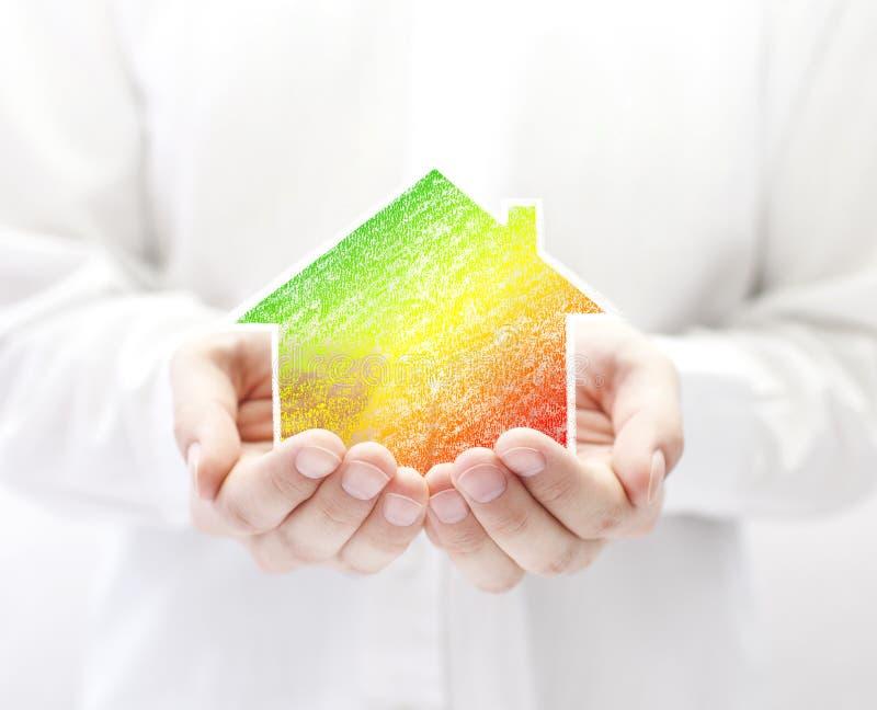 Buntes Haus in den Händen Energiesparendes Konzept lizenzfreie stockfotografie