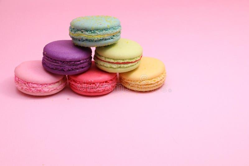 Buntes Kuchenmacaron oder -makrone auf rosa Hintergrund von der Draufsicht, buntes Mandelgebäck, Pastellfarben, Weinlesekarte stockbild