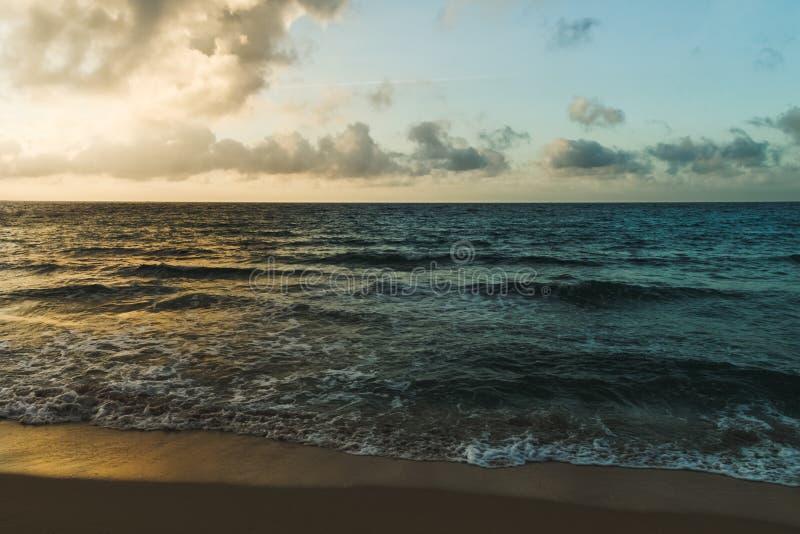 Buntes Licht des Sonnenuntergangs nachdenkend über die Wellen am Strand von stockfotografie