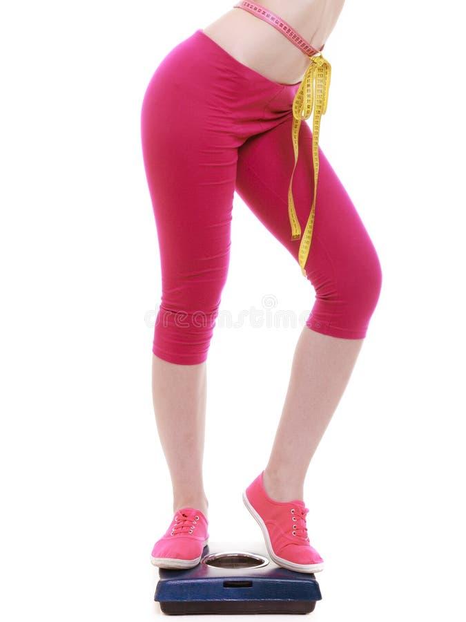 Buntes messendes Band auf Frauenkörper, geeignetes Mädchen, das ihre Taille steht auf Skala misst lizenzfreie stockbilder