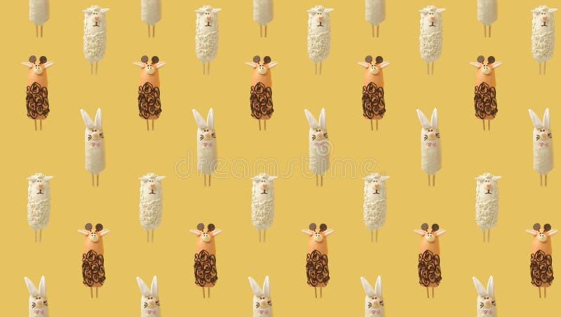 Buntes Muster, das aus Bananen in der Schokolade in Form von verschiedenen Tieren auf gelbem Hintergrund besteht Von der Draufsic stockbild