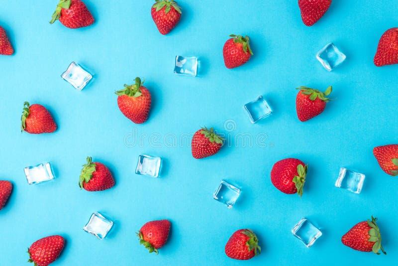 Buntes Muster gemacht von den Erdbeeren mit Eisw?rfeln auf blauem Hintergrund Minimales Sommerkonzept lizenzfreies stockbild