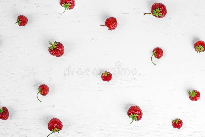 Buntes Muster von Erdbeeren auf weißem hölzernem Hintergrund Beschneidungspfad eingeschlossen stockfoto