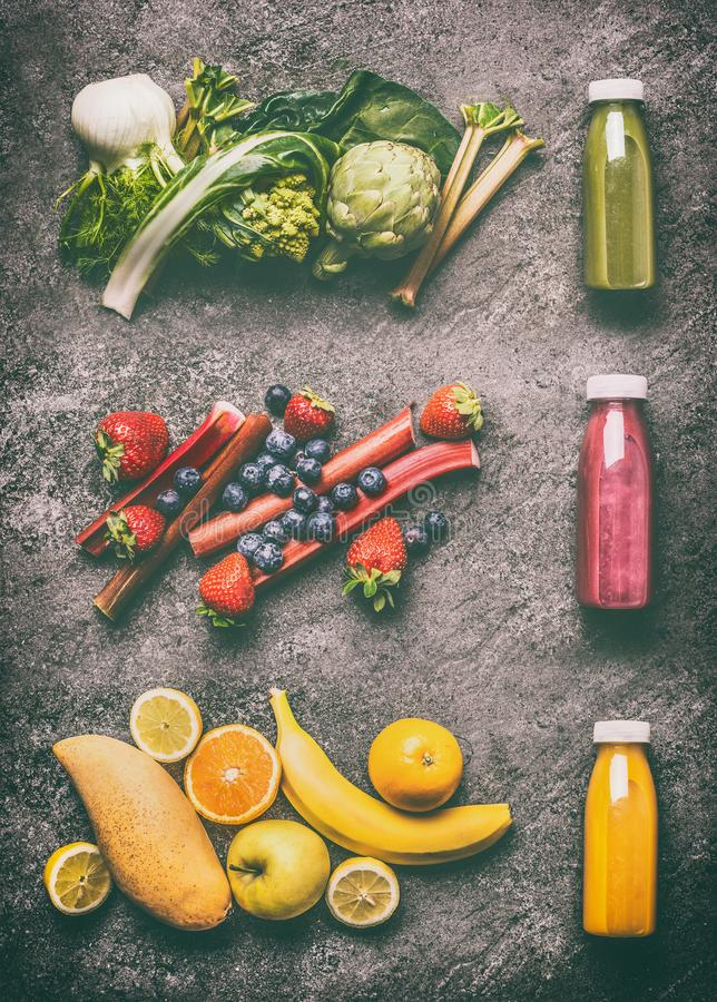 Buntes organisches Gemüse, Früchte und Beeren Smoothies mit Bestandteilen in den Flaschen auf dunkelgrauem Granittisch, Draufsich stockfoto