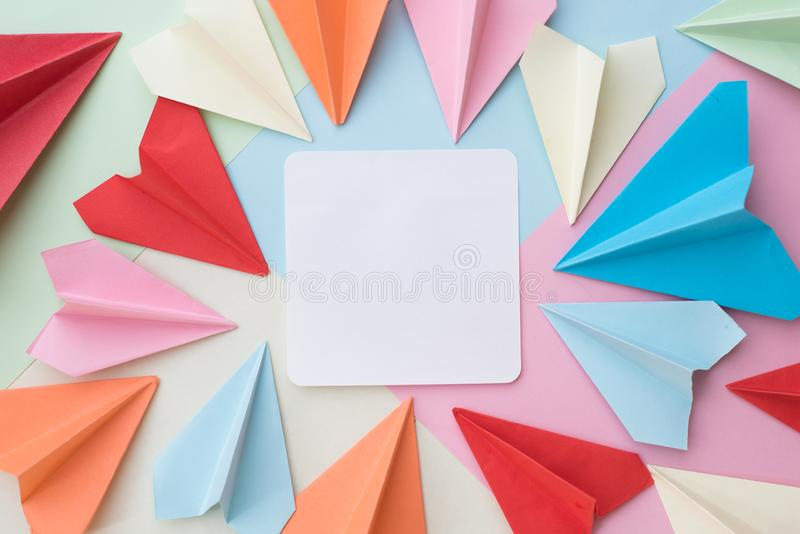 Buntes Papierflugzeug und leere weiße Notiz tapezieren Auflage auf buntem Pastellhintergrund lizenzfreies stockfoto