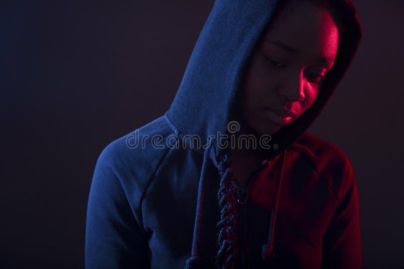 Buntes Porträt der durchdachten Frau mit dunkle Haut tragendem Hoodie lizenzfreie stockfotos