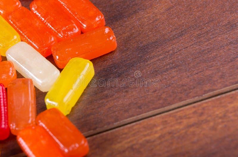 Buntes rechteckiges Bonbon der Nahaufnahme, das auf Holzoberfläche liegt stockfotos