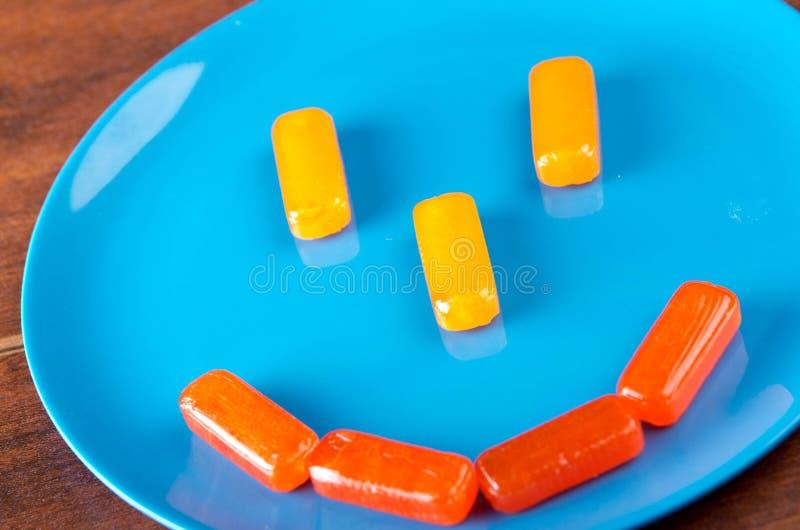 Buntes rechteckiges Bonbon gesetzt als smileygesicht auf blaue Platte mit Holzoberflächehintergrund stockfotografie
