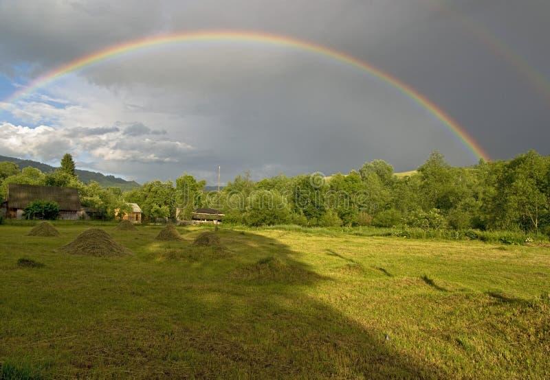 Buntes Regenbogenrecht unter Ebene in den alten großen Bergen stockfotografie