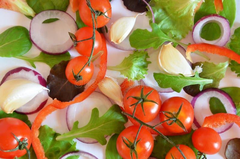 Buntes Salatbestandteilmuster gemacht von den Tomaten, Ruccola, Ringe der purpurroten Zwiebel, roter Gemüsepaprika, Paprika, Knob stockbild