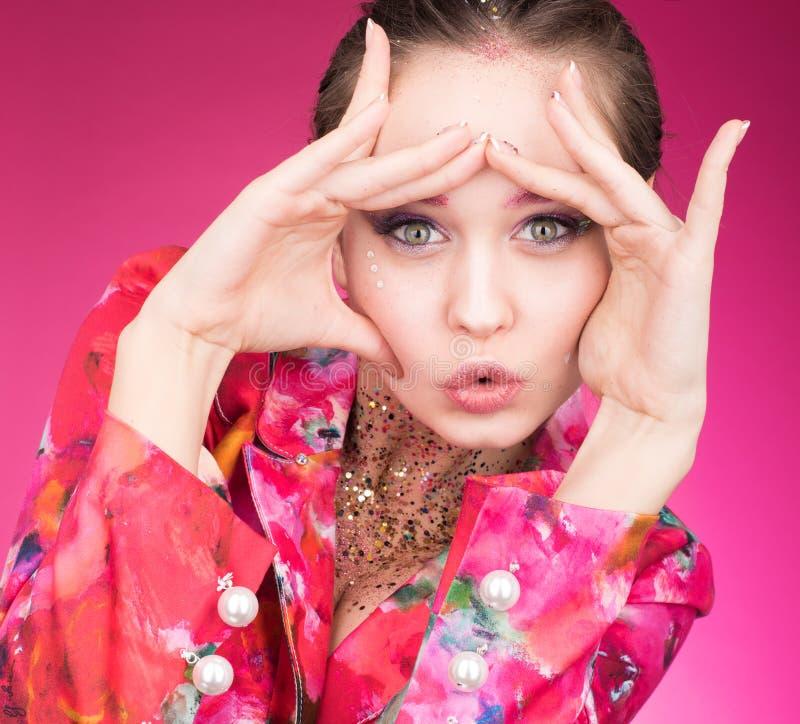 Buntes Studioporträt der jungen Frau aufwerfend in einer hellen Jacke Schauen durch die Hände stockfoto