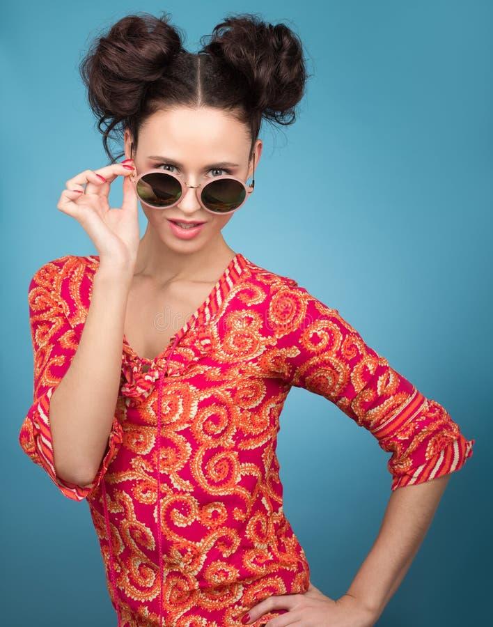 Buntes Studioporträt der jungen Frau in der Sonnenbrille Helle rote Bluse stockfoto