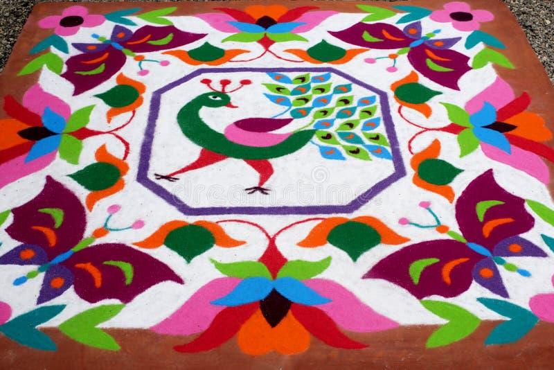 Buntes traditionelles Blumenmuster Rangoli gemacht mit trockenen pulverisierten Farben mit Pfau, Blumen und Schmetterlingen stockbilder