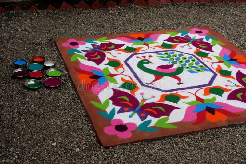 Buntes traditionelles Blumenmuster Rangoli gemacht mit trockenen pulverisierten Farben mit Pfau, Blumen und Schmetterlingen stockbild