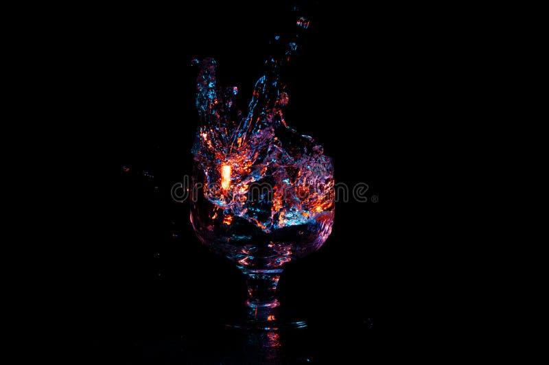 Buntes Wasser, das in das Glas lokalisiert auf einem schwarzen Hintergrund gegossen wird stockbilder
