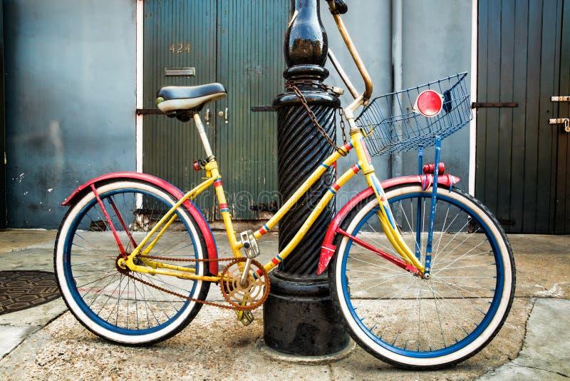 Buntes Weinlese-Fahrrad, das auf einem New- Orleanslaternenpfahl sich lehnt lizenzfreies stockfoto